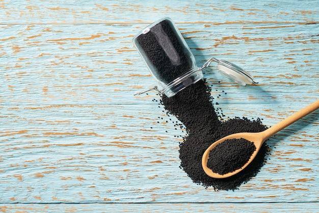 I semi di cumino neri vengono versati da un barattolo di vetro in un cucchiaio di legno