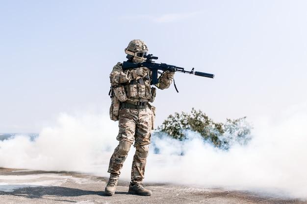 I soldati dell'esercito americano sono una zona di guerra con un fucile d'assalto in un denso fumo di granate fumogene