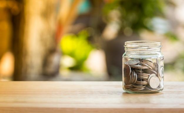 I soldi coniano in barattolo di vetro per il risparmio e il concetto di investimento finanziario