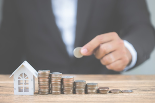 I soldi della pila della moneta aumentano lo sviluppo crescente con la casa bianca di modello sulla tavola di legno.