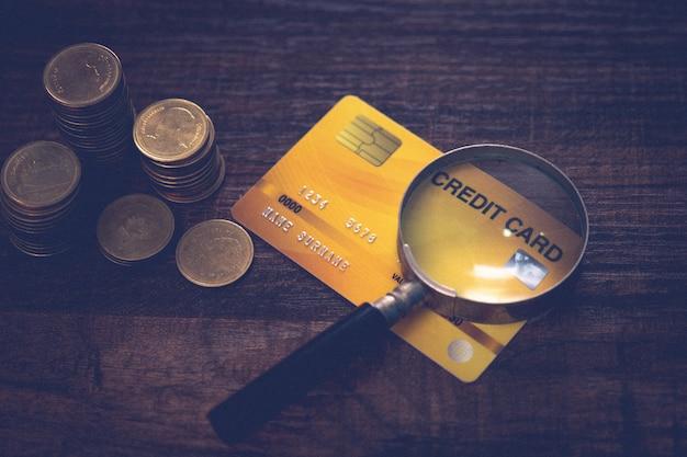 I soldi di affari coniano con la carta e la lente d'ingrandimento sulla tavola di legno, sull'ufficio di credito e sull'approvazione di credito finanziaria