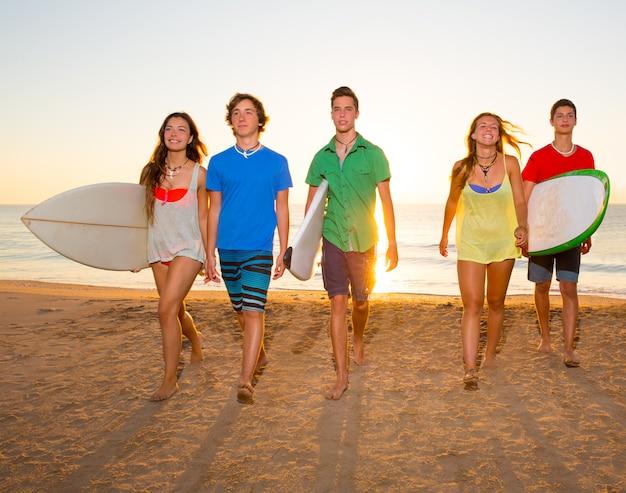 I surfisti ragazzi e ragazze raggruppano camminando sulla spiaggia