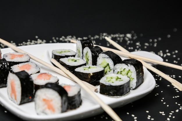 I sushi hanno messo con la vista laterale del sesamo del riso di color salmone del cetriolo