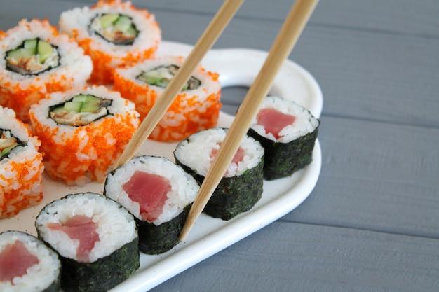 I sushi hanno messo con le bacchette sulla tabella di legno grigia