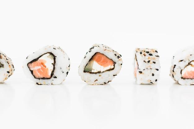 I sushi rotolano la fila contro fondo bianco