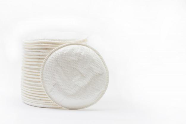 I tamponi di cotone rotondi inseriscono il reggiseno per le madri che allattano su bianco con copyspace