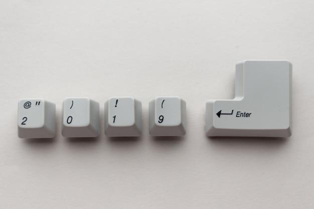 I tasti della tastiera bianca 2019 immettono i pulsanti su sfondo grigio neutro. carta del nuovo anno di concetto. co