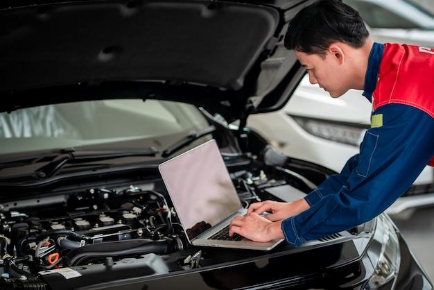 I tecnici controllano e riparano le auto in garage i tecnici nell'officina riparazioni auto utilizzano i sistemi informatici per verificare i problemi del motore: servizi di riparazione di automobili, concetti di manutenzione.
