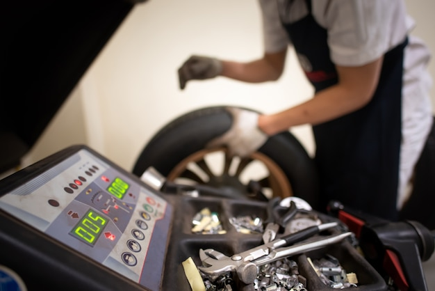 I tecnici dell'assistenza stanno cambiando le gomme utilizzando una macchina equilibratrice con servizi di manutenzione.