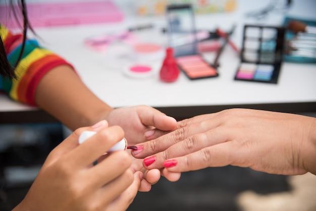 I tecnici delle unghie stanno facendo l'unghia nel salone con cosmetici in background.