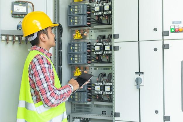 I tecnici di manutenzione asiatici ispezionano il sistema di protezione del relè con un computer portatile. baia cont