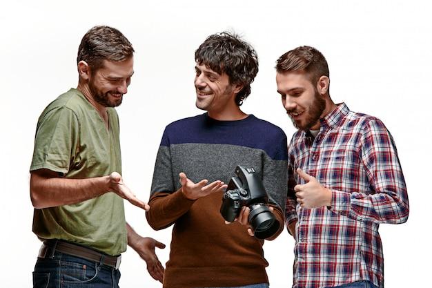 I tre amici maschii con la macchina fotografica su bianco