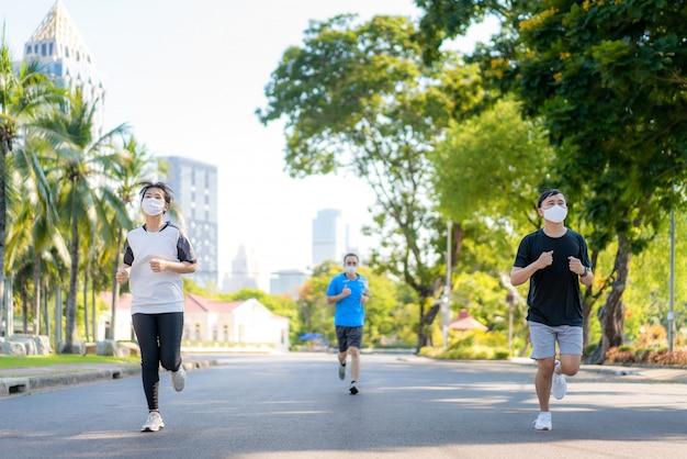 I tre giovani asiatici donna e donna sono jogging e accise all'aperto nel parco della città e indossando maschera protettiva sul viso per rimanere in forma durante la pandemia di covid-19 a bangkok, in thailandia.