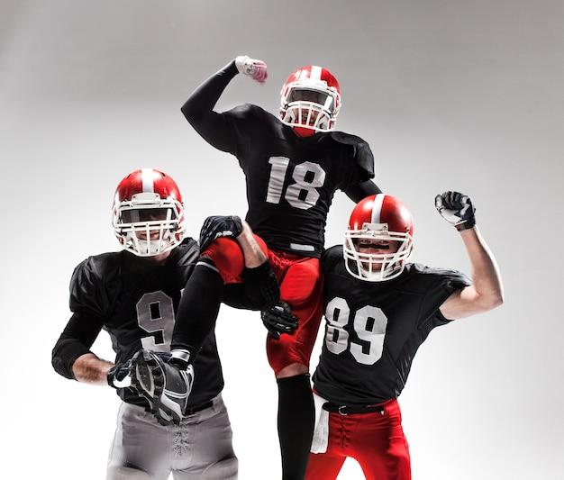 I tre uomini di fitness caucasici come giocatori di football americano in posa come vincitori su bianco e gioia