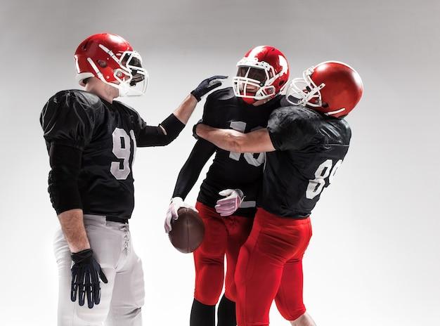 I tre uomini di fitness caucasici come giocatori di football americano in posa come vincitori su sfondo bianco e gioia