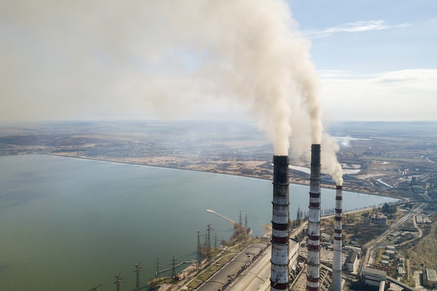 I tubi alti della centrale elettrica, il fumo bianco su paesaggio rurale, l'acqua del lago e il cielo blu copiano lo spazio.