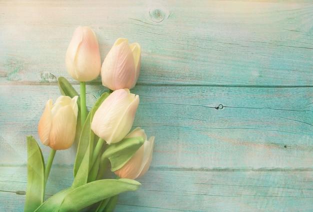 I tulipani rosa della primavera fioriscono su legno