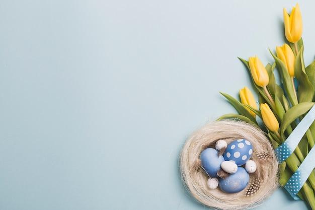 I tulipani si avvicinano al nido con le uova colorate