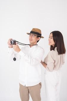 I turisti asiatici delle coppie stanno godendo sulla parete bianca