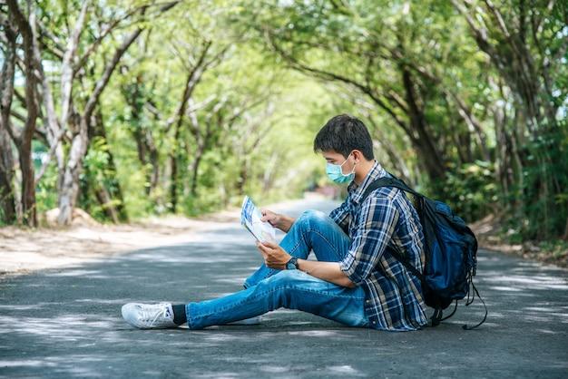 I turisti di sesso maschile si siedono e guardano la mappa sulla strada.