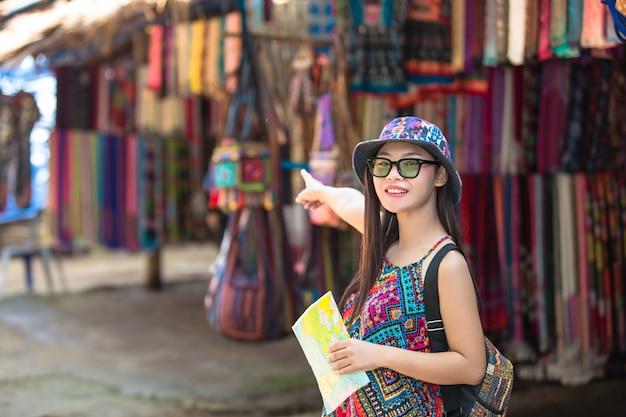I turisti femminili a disposizione hanno una mappa di viaggio felice.