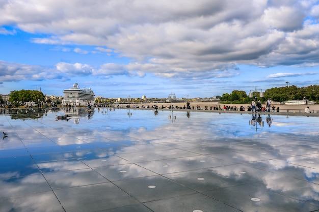 I turisti godono la loro vacanza sul mirorr acqua di bordeaux con la famosa nave da crociera olandese sul retro
