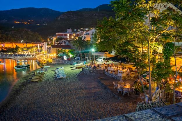 I turisti hanno visitato i ristoranti sul mare adriatico per una cena romantica durante il tramonto.