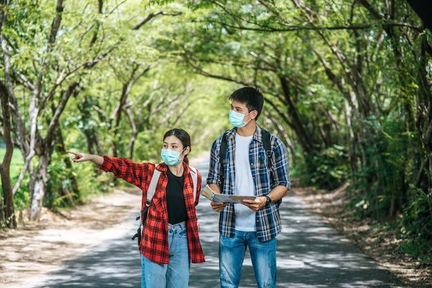 I turisti maschi e femmine indossano maschere mediche e guardano la mappa sulla strada.