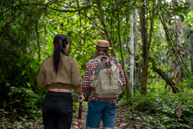 I turisti maschi e femmine si godono la foresta.