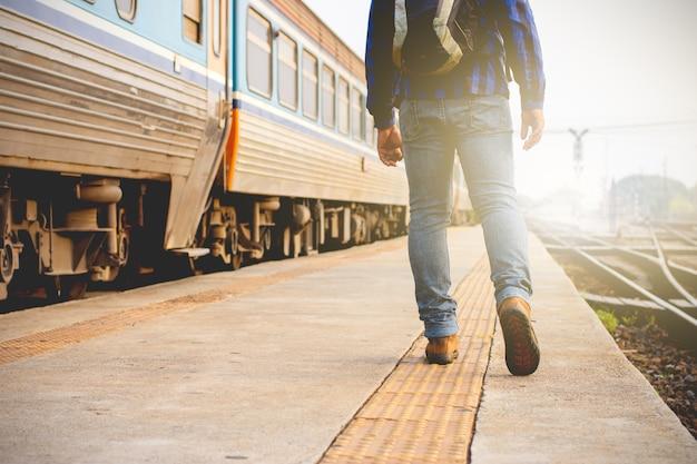 I turisti maschi stanno camminando alla stazione ferroviaria.