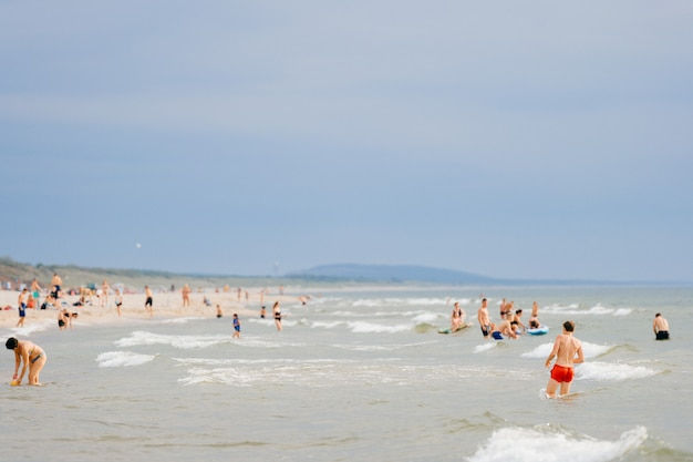 I turisti si rilassano nel mare e sulla spiaggia sabbiosa