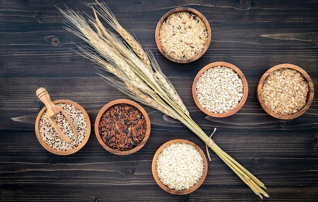 I vari cereali organici naturali e gli interi semi seminano in ciotola di legno per il concetto di prodotto sano dell'ingrediente di alimento.