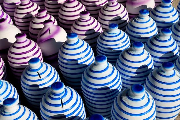 I vasi di argilla fatti a mano tradizionali variopinti con dipinto nelle linee intorno hanno riunito nell'ambito della luce solare di mattina e del fondo dell'ombra