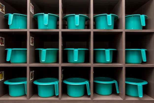 I vasi turchesi per bambini stanno in fila su un rack nell'asilo del bagno