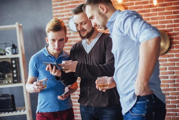 I vecchi amici allegri comunicano tra loro e guardano il telefono, bicchieri di whisky nel pub. stile di vita di intrattenimento. wifi collegato persone nella riunione del tavolo da bar