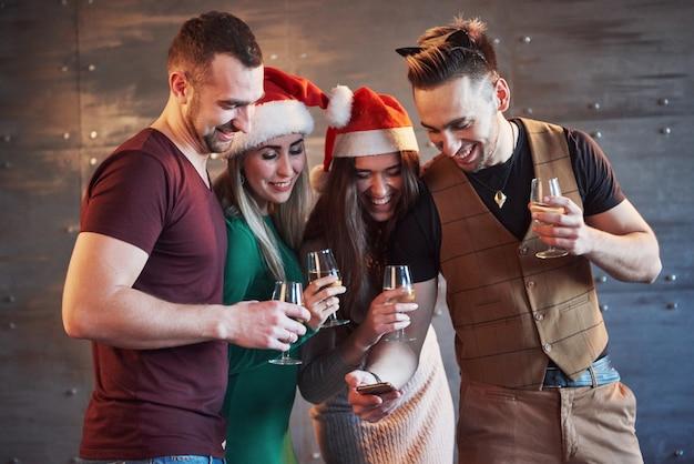 I vecchi amici allegri comunicano tra loro e guardano il telefono, con bicchieri di champagne nella festa di capodanno. concetto di intrattenimento e stile di vita. wifi connesso persone