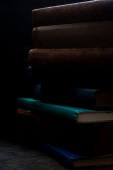 I vecchi libri impilano su superficie di legno antica nella luce direzionale calda