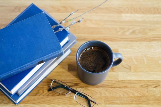 I vecchi libri sono impilati su un tavolo di legno. tra le pagine chiuse ramoscello di salice. sul tavolo ci sono bicchieri soft focus e una tazza di caffè è in piedi.