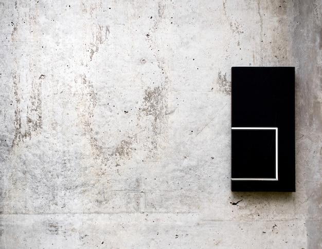I vecchi muri di cemento sono decorati con un piatto di legno nero
