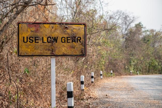I vecchi segnali stradali sono arrugginiti usare basso ingranaggio e ripidi segnali di avvertimento per i camion sulle montagne