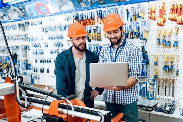 I venditori stanno lavorando nel negozio di utensili elettrici
