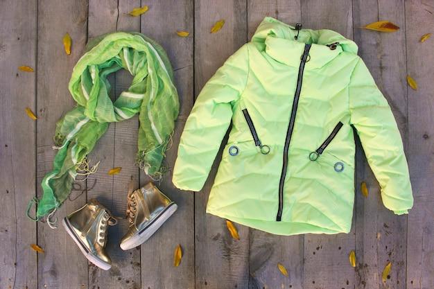 I vestiti dell'autunno dei bambini sul pavimento di legno con le foglie