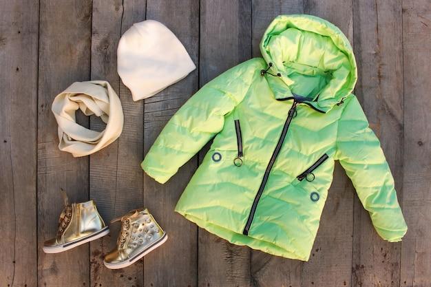 I vestiti dell'inverno dei bambini sulla vecchia tavola di legno. vista dall'alto. disteso.