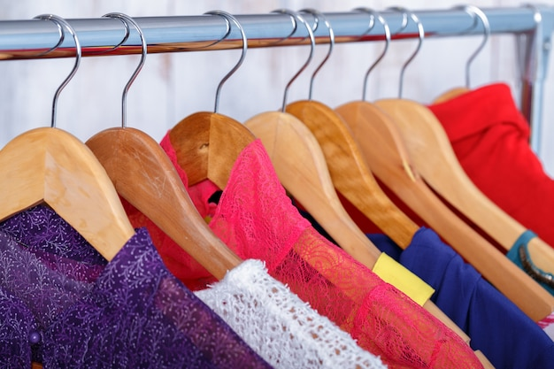 I vestiti delle donne variopinte sui ganci sullo scaffale nel deposito di modo. wom