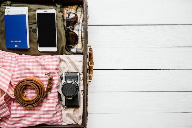 I vestiti e gli accessori d'annata dei pantaloni a vita bassa hanno imballato in valigia per il viaggio sulla tavola di legno bianca con lo spazio della copia