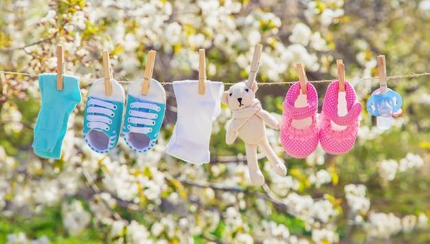 I vestiti e gli accessori per bambini pesano sulla corda dopo il lavaggio all'aria aperta. messa a fuoco selettiva