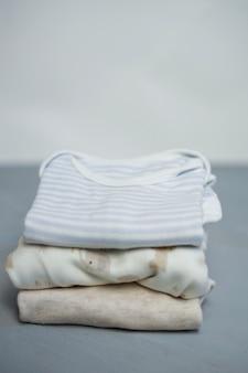 I vestiti piegati cotone variopinto impilano sul fondo vuoto dello spazio della tavola bianca, lavanderia del bambino.