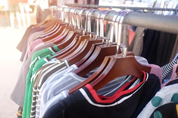 I vestiti variopinti che appendono sul clothesline e hanno luce solare arancione splende.