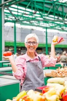 I vetri d'uso della bella donna senior vende il pepe sul mercato