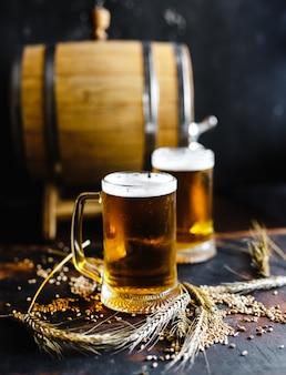 I vetri di birra e il grano aromatizzano su una vecchia tavola di legno rustica su fondo nero